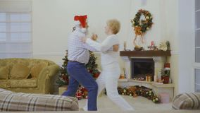 Happy mature woman dancing with husband near Christmas tree at home