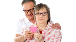 Old couple facing camera with focus on paper heart Stock Images