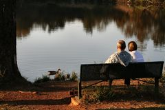 Old couple feeding ducks. People royalty free stock photos