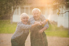 Old couple with garden hose. Cheerful women and men outdoors stock image
