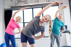 Old couple and girl exercising in fitness class for kids and senior people Royalty Free Stock Photo