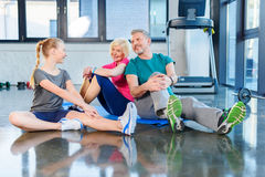 Old couple and girl stretching in fitness class for kids and senior people Stock Photography