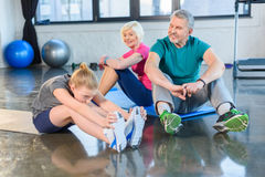 Old couple and girl stretching in fitness class for kids and senior people Royalty Free Stock Photo