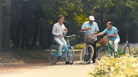 Old couple has a rest and drinks water when riding on bicycles in park. Senior sporty couple and young man stand near their bicycles in the park. Pleasant stock video