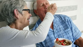 Old couple having breakfast in bed stock video footage