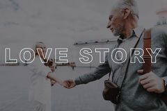 Old Couple Hold Hand. Man with Film Camera. stock photo