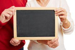 Old couple holding blackboard in hands Stock Images