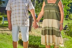 Old couple holding hands. stock photo