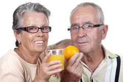 Old couple holding an orange juice and  one orange Stock Image