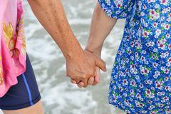 Old couple holds hand along the beach Stock Image