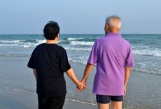 Old couple holds hand along the beach Stock Photo