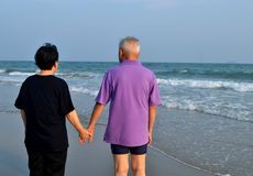 Old couple holds hand along the beach Royalty Free Stock Photo