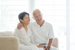 Old couple at home, looking away. Portrait of happy Asian elderly couple at home, looking away, old senior retired people indoor lifestyle stock image