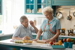 Old couple in kitchen. Wife rolls out dough for a pie, while husband drinks juice and talking to her. Cooking, retirement royalty free stock photo