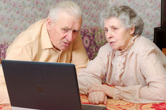 Old couple look to the laptop with active interest. And speak Royalty Free Stock Photography