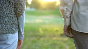 Old couple looking into future, standing apart in park indifference and break-up. Stock photo stock images
