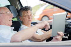 Old couple lovers using tablet in car travel. Old couple lovers using tablet in the car travel Royalty Free Stock Images