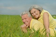 Old couple lying on the field. Beauteous old couple lying on the field stock photography