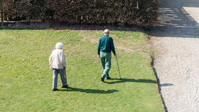Old couple walking in the park Stock Photos
