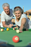 Old couple playing billiard Stock Images