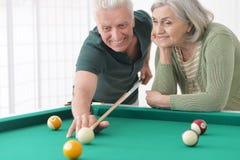 Old couple playing billiard Stock Photo