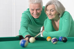 Old couple playing billiard Stock Photography