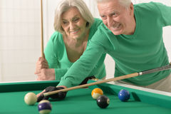Old couple playing billiard Royalty Free Stock Photo