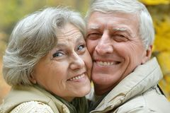 Old couple posing at autumn park Royalty Free Stock Photos