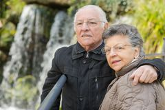 Old couple posing next to waterfalls Stock Photo