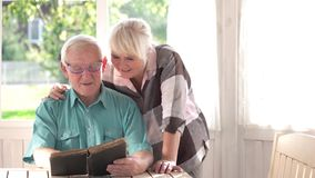 Old couple reading a book. Lady smiling to a man. Stories from the past stock video