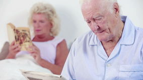 Old couple reading a book and newspaper Royalty Free Stock Photos