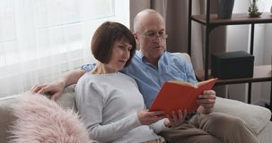 Old couple reading a book on sofa at home. Old couple reading a book while sitting on sofa at home stock video