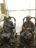 Old couple relaxing in the sunroom. An elderly couple of statues relaxing in their sun room.  He reads the paper while she knits royalty free stock photography