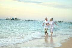 Old couple running on sea beach Royalty Free Stock Photos