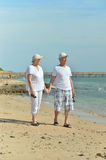 Old couple on sea beach Stock Photos