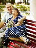 Old couple sit on bench. Stock Photos
