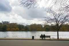Old couple sit on bench in park stock photo