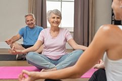 Old couple sitting in lotus position. Senior couple with trainer sitting in lotus position meditating. Instructor with old men and elderly women doing yoga at stock photo