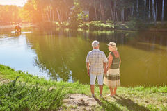 Old couple standing near water. Senior people, summer nature Stock Photo
