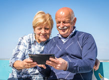 Old couple. With tablet on the beach stock image