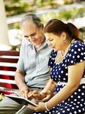 Old couple with tablet pc sit on bench . Stock Image