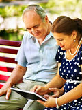 Old couple with tablet pc sit on bench . Royalty Free Stock Images