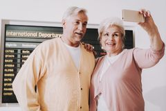Old Couple Taking Photo in Airport in Waiting Room stock photography
