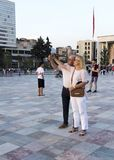 Old couple taking self-portraits in skandebeg square Royalty Free Stock Photography