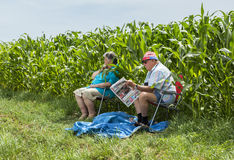 Old Couple - Tour de France 2015. QUIEVY,FRANCE- JULY 07, 2015: Unidentified old couple sitting by the corn field and waiting for the peloton during the stage Royalty Free Stock Photos