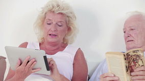 Old couple using a tablet and book Royalty Free Stock Image