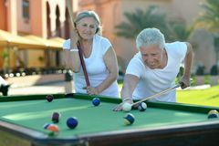 Old couple on vacation playing billiards Royalty Free Stock Image