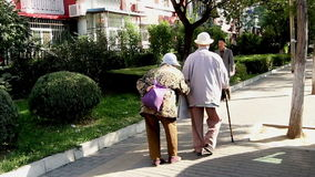 The old couple walk on the street