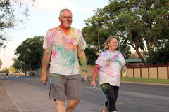 Old couple walking covered with powder paint at colour run Stock Images