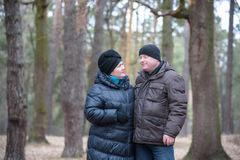Old couple walking in the forest. Having a good time together. Smiling and talking on autumn or spring Stock Photo